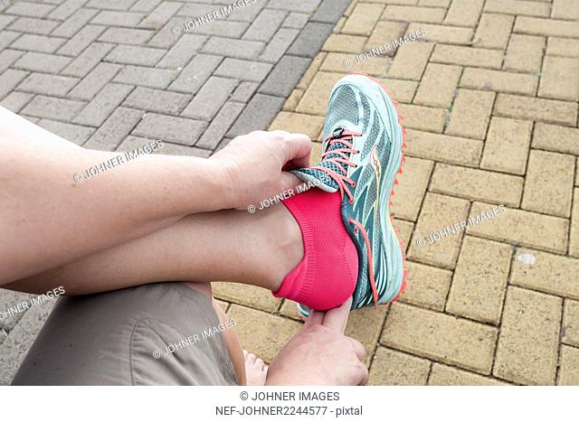 Woman putting shoes on