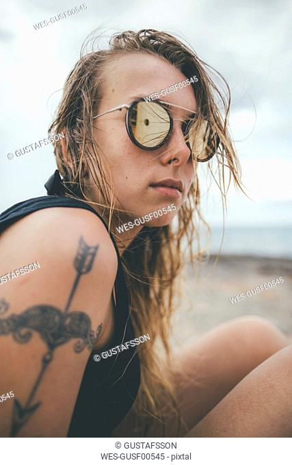Portrait of a young woman with sunglasses and a tattoo