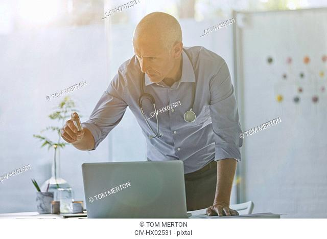 Male doctor examining prescription medication at laptop in doctor's office