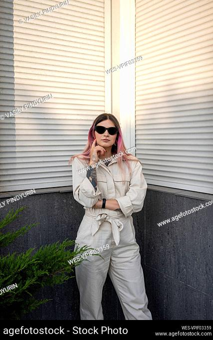 Confident woman with tattoo wearing sunglasses against built structure