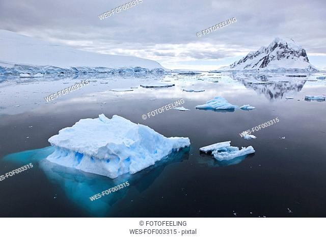 South Atlantic Ocean, Antarctica, Antarctic Peninsula, Lemaire Channel, View snow coverd mountain range and iceberg