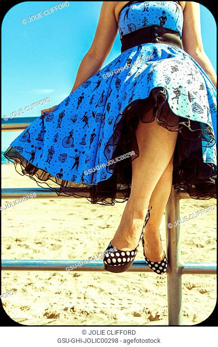 Young Adult Woman in Retro Dress and High Heels Sitting on Railing at Beach