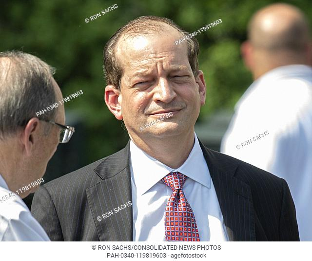 United States Secretary of Labor Alex Acosta converses with an unidentified person as he awaits the arrival of US President Donald J