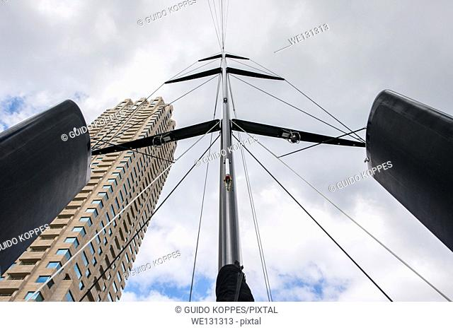 Rotterdam, Netherlands. Mast of a sailboat racer, against a cloudy sky and the Montevideo Tower, docked at the Rotterdam Wilhelminapier