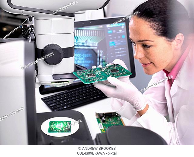 Engineer using 3D servo microscope to view dimensional accuracy of manufactured PCB assembly