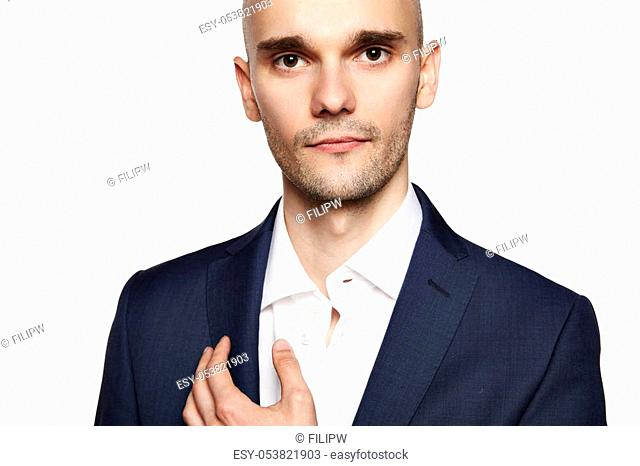Close-up portrait of a handsome bald man looking at camera. White background. Horizontal
