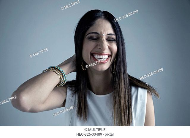 Portrait brunette Indian woman wearing bindi laughing with eyes closed