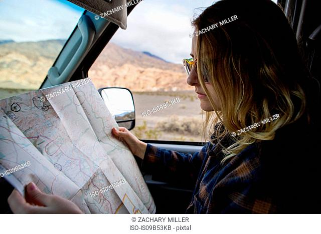 Woman reading map in car, Death Valley National Park, California, US