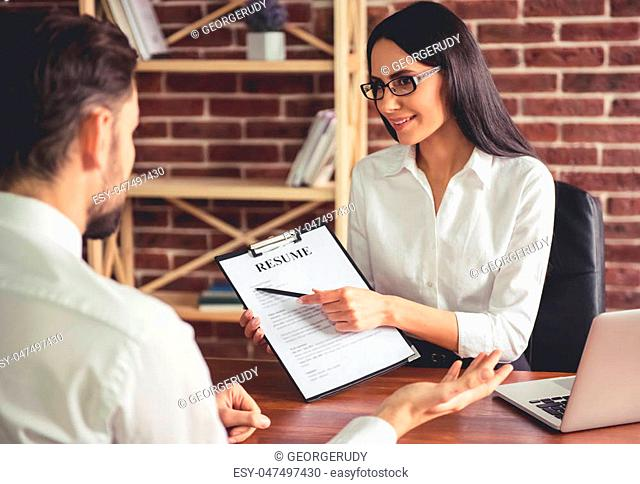 Beautiful female employer in suit is conducting a job interview while sitting in her office