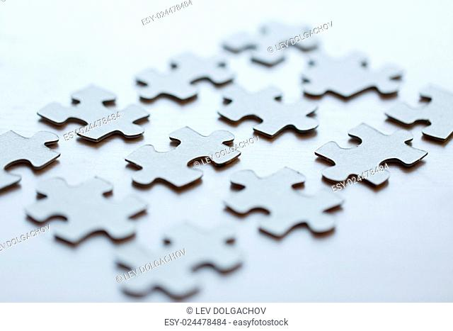 business and connection concept - close up of puzzle pieces on table