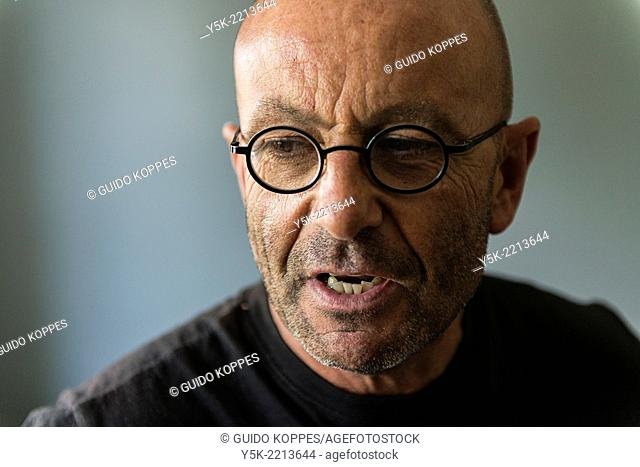 Tilburg, Netherlands. Studio-portrait of a bald, be glassed and middle-aged man, talking, speaking and telling a story