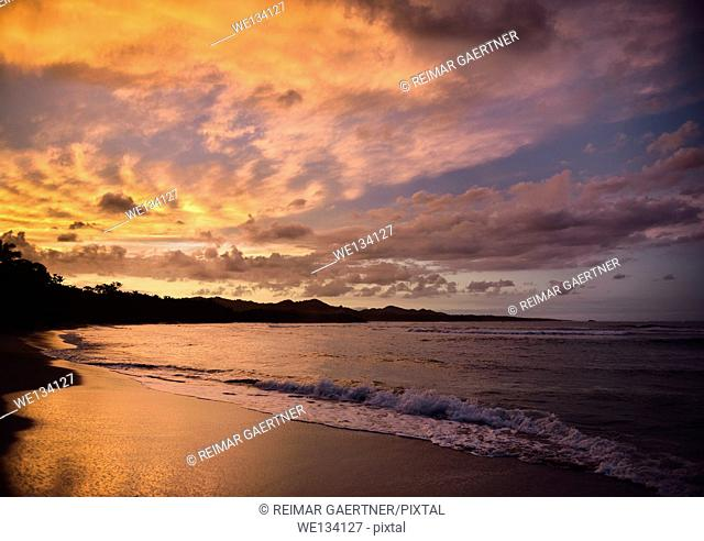 Golden clouds at sunset reflecting off wet beach sand Maimon Bay Dominican Republic