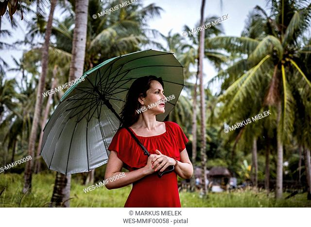 Thailand, Koh Phangan, portrait of woman strolling with umbrella