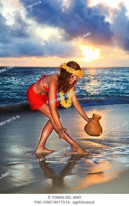 Hawaii, Oahu, Lanikai, Beautiful Hawaiian woman dancing hula on ocean shoreline