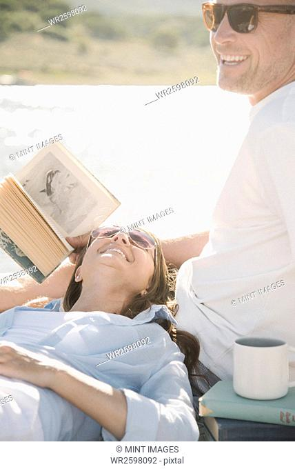 Man and woman reclining on a jetty, reading a book