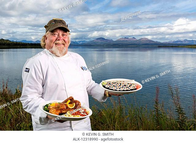 Tikchik Narrows Lodge Chef, Matt Spence, holding his Peking Duck and Sushi rolls on the shore of Tikchik Lake, Wood-Tikchik State Park, Southwest Alaska, USA