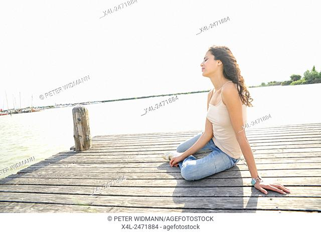 Young, pretty woman at the dock on Lake Neusiedl, Austria, Burgenland, Jois