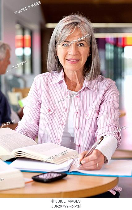 Smiling mature student studying textbook
