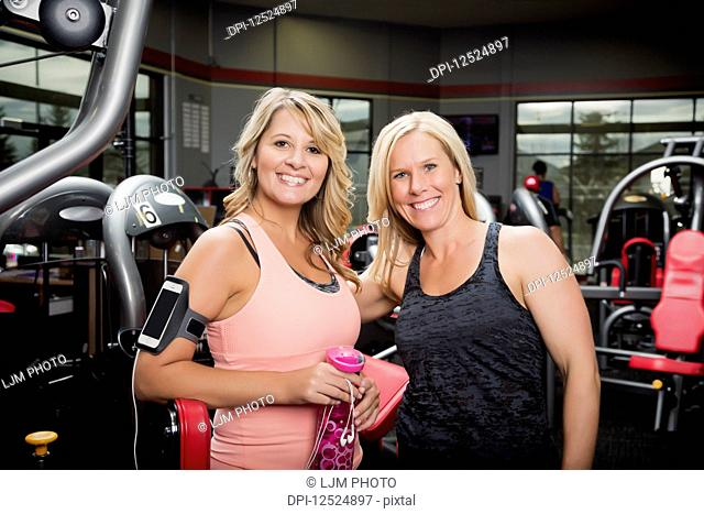 A personal trainer and her client pausing and posing for the camera after working out at a fitness facility; Spruce Grove, Alberta, Canada