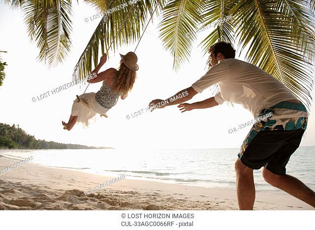 Man pushing swinging woman at beach
