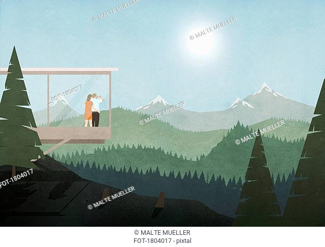Couple looking at idyllic, sunny mountain and forest view from glass house