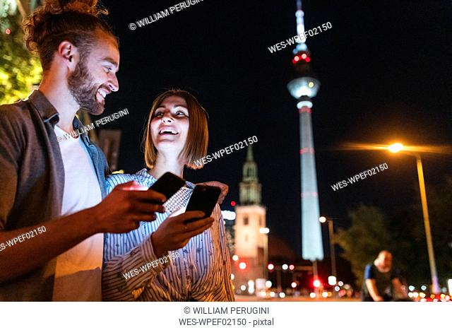 happy couple using smartphones in the city at night, Fernsehturm in the background, Berlin, Germany
