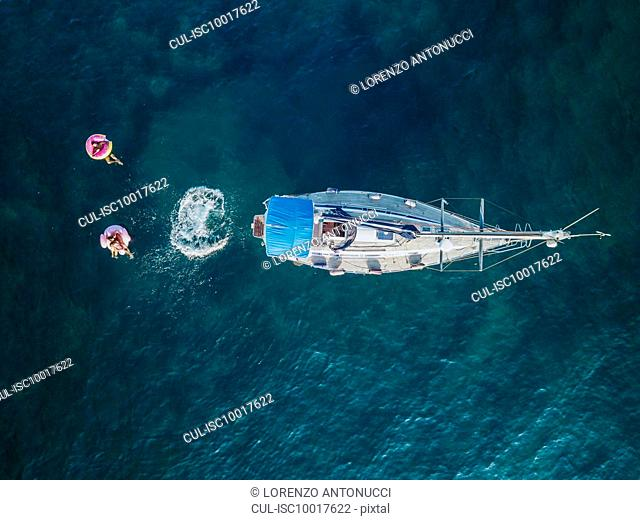 Holiday makers swimming off sailboat on sea, Italy