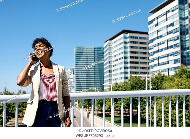Businesswoman using smartphone, with office buildings in the background