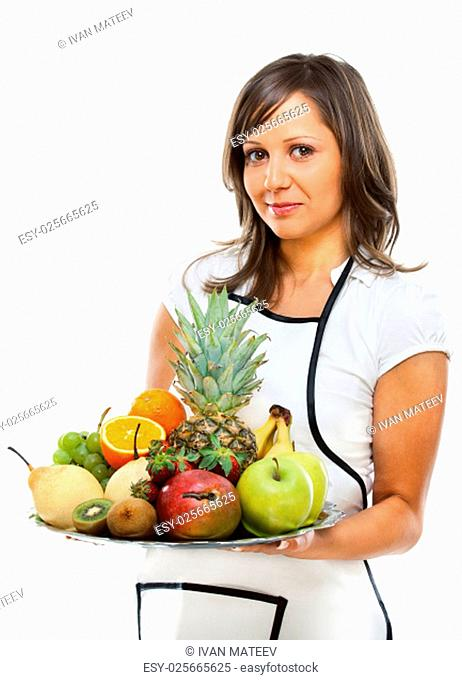 Young woman holding a tray with fresh fruits - apples, pears, grapes, pineapple, oranges, kiwi, strawberries and others