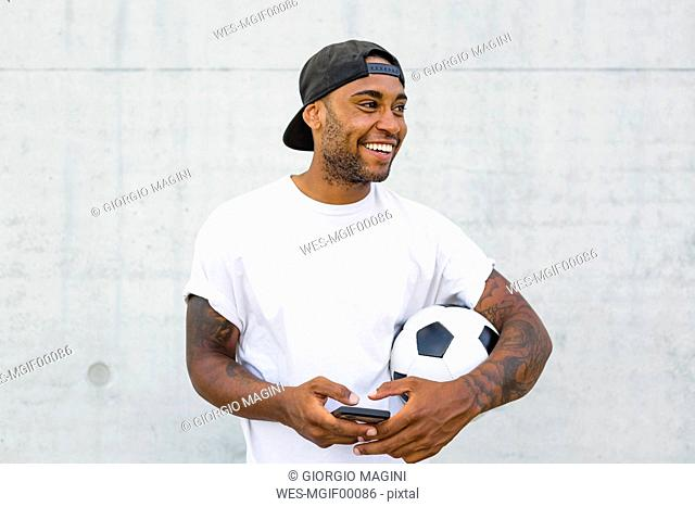 Portrait of laughing young man with soccer ball and cell phone