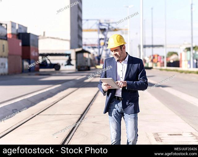 Businessman wearing safety helmet using digital tablet at industrial site
