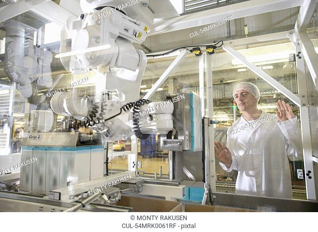 Worker with machinery in biscuit factory