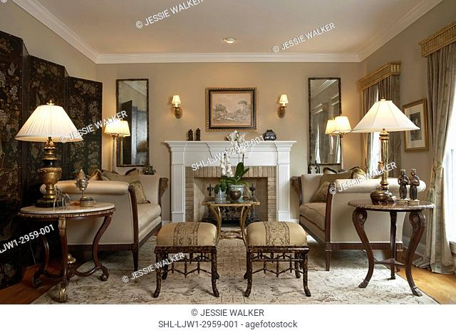 Living room with formal furniture, lamps, fireplace, draperies under gold leaf cornices, symmetry, pairs of sconces, lamps, mirrows, ottomans, sotas