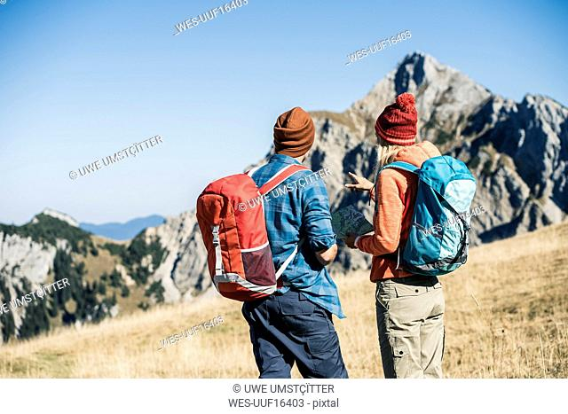 Austria, Tyrol, couple with map hiking in the mountains