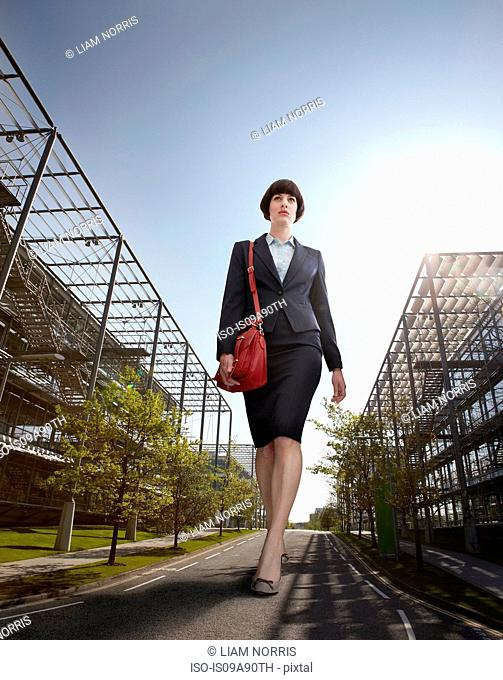 Oversized businesswoman walking on road, low angle view