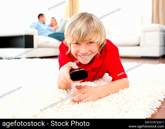 Happy boy holding a remote lying on the floor