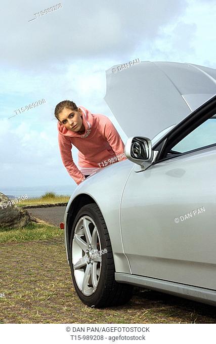 A woman by a broken down car