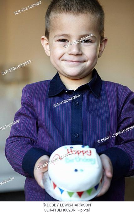 Boy holding miniature cake