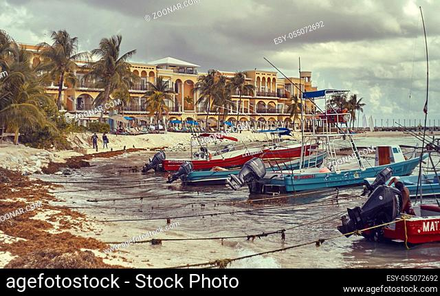 Several small fishing boats are moored by the sea in the beautiful beach of Playa del Carmen in Mexico with the background of the typical buildings of this...