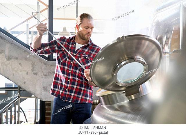 Male Brewery Worker Checking Fermentation Process In Steel Vat