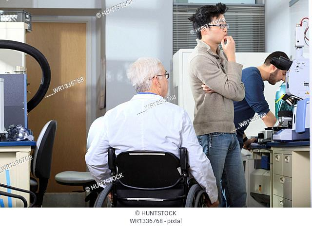 Professor with muscular dystrophy working with engineering student looking at x-ray fluorescence analyzer in a laboratory