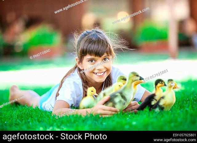 Cute girl lying down on grass and holding spring ducklings
