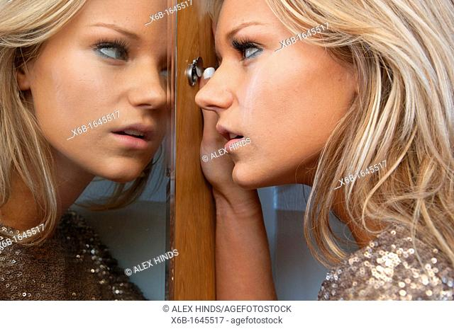 Young woman, 18-25 years, looking through hotel room door security spy peep hole