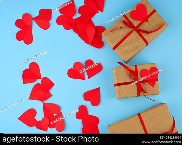 rectangular box is wrapped in brown paper and tied with a red thin silk ribbon on a blue background, red cut out paper hearts, copy space