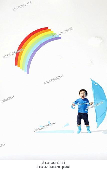 Boy Playing Under Rainbow