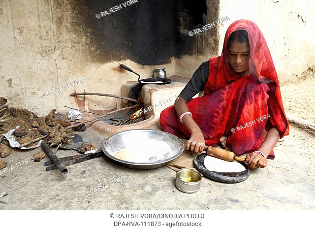 A  woman making wheat bread or rotis  on a fireplace  ; Rajasthan ; India