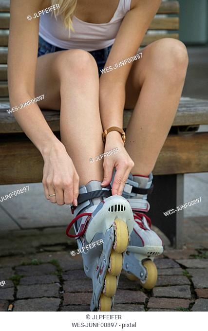 Young woman sitting on bench tying her inline skates, partial view