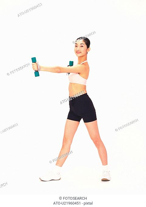 Image of a Young Adult Woman Posing and Lifting Some Weights, Smiling, Looking at Camera, Side View