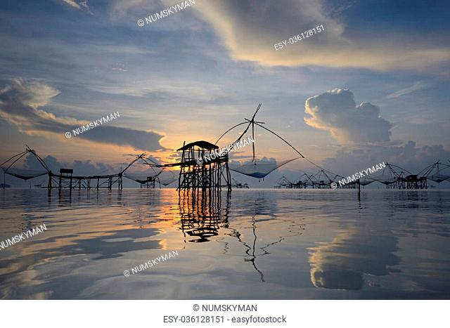silhouette traditional fishing method using a bamboo square dip net with sunrise background in Patthalung, Thailand