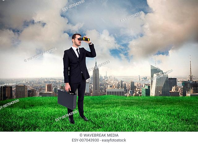 Composite image of businessman holding a briefcase while using binoculars